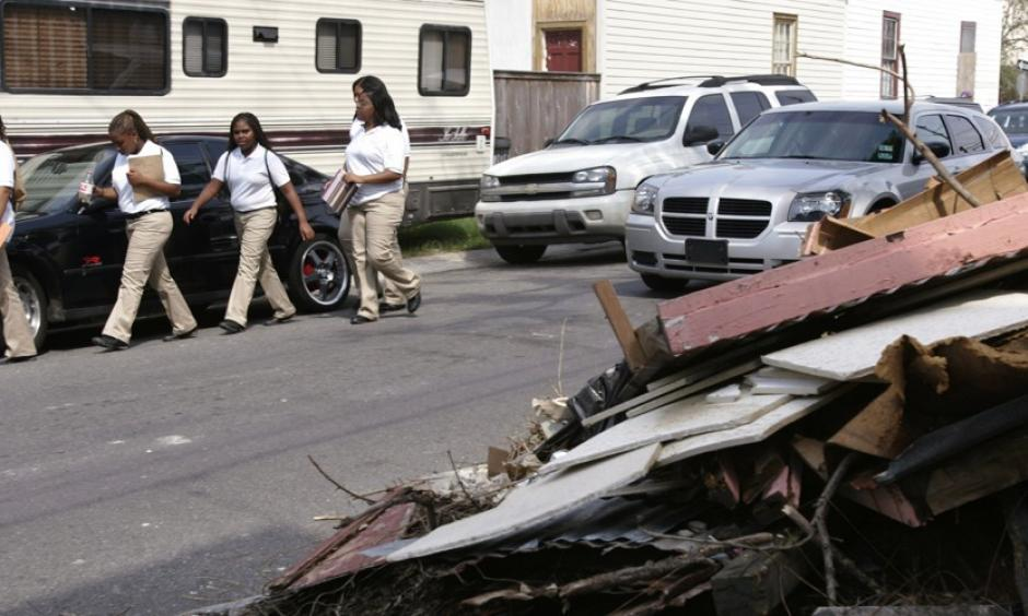 Students walk next to a pile of debris. Students walk past a debris pile from a house damaged during Hurricane Katrina. Photo: Lee Celano, Reuters
