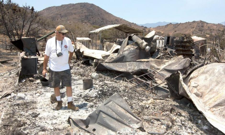 Steve Keeling walks through the ashes of his fire ravaged home, Monday, June 27, 2016, in South Lake. California. Photo: Rich Pedroncelli, AP
