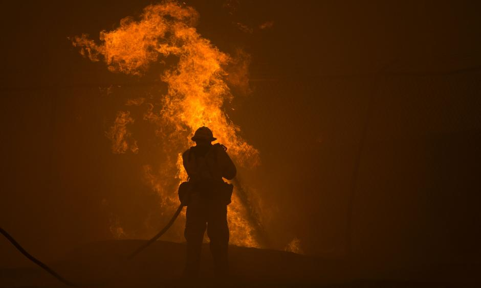 A firefighter hosed down burning pipes on Saturday near Santa Clarita, Calif. Photo: David McNew / Agence France-Presse — Getty Images