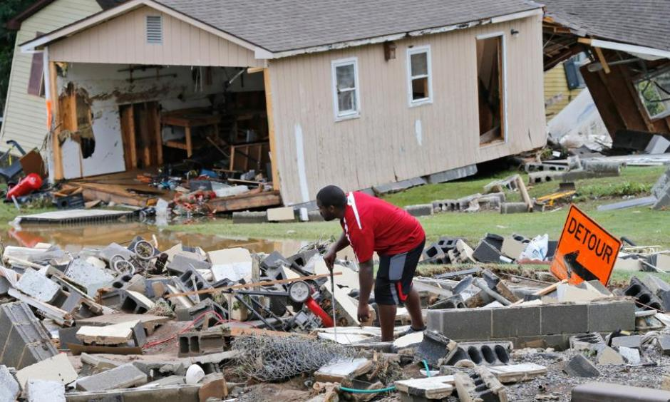 A White Sulphur Springs resident sorts through debris as the cleanup begins from severe flooding in White Sulphur Springs, West Virginia. Photo: Steve Helber, AP