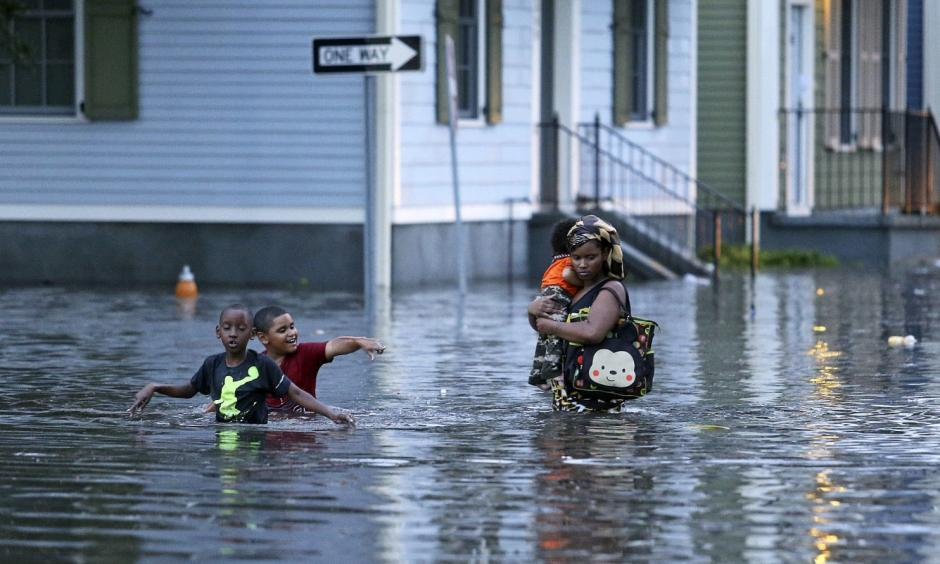This Saturday, Aug. 5, 2017 photo shows a woman carrying an infant through floodwaters as two boys tag along in Metairie, La. Photo: Michael DeMocker, NOLA.com/The Times-Picayune via AP