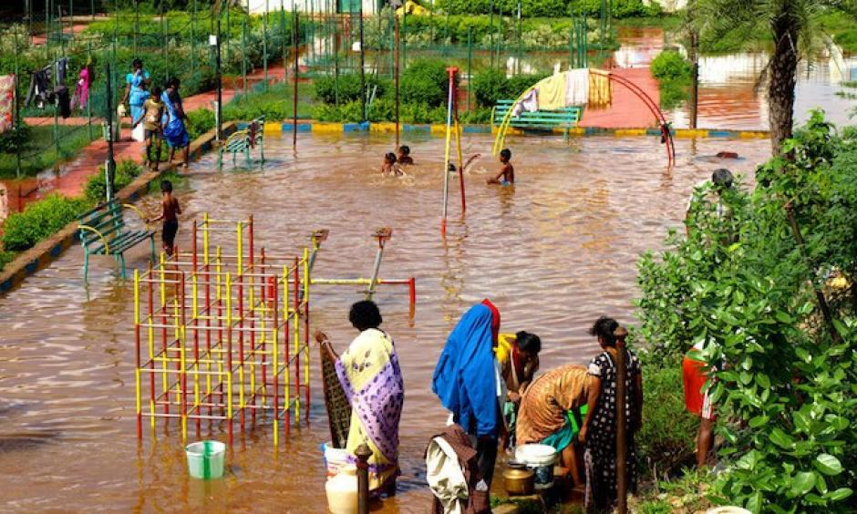 Children using a flooded playground as a swimming pool in Chennai. Photo: Ben Robinson