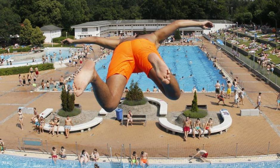 A young boy jumps from a 7.5 meter platform at a crowded outdoor pool during a record heat wave in Frankfurt, Germany, Friday, July 3, 2015. Photo: Michael Probst, AP