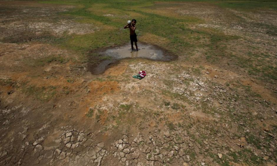 A village boy baths in the remaining water of a dried pond to beat the heat in the outskirts of the eastern Indian city of Bhubaneswar on April 23, 2016. Photo: Getty Images