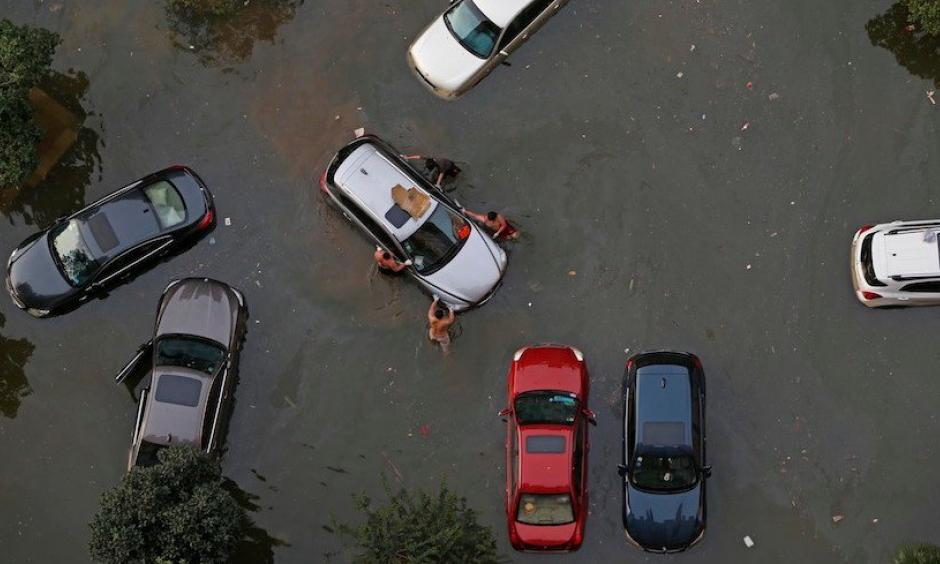 Vehicles are submerged in floodwaters on July 9, 2016 in Wuhan, Hubei Province of China. Many parts of the Wuhan area were submerged in floodwaters during July as torrential rains affected the Yangtze River valley. A new study finds that climate change increased the risk of the rains that led to the flooding by 17 – 59%. Photo: VCG/VCG via Getty Images.