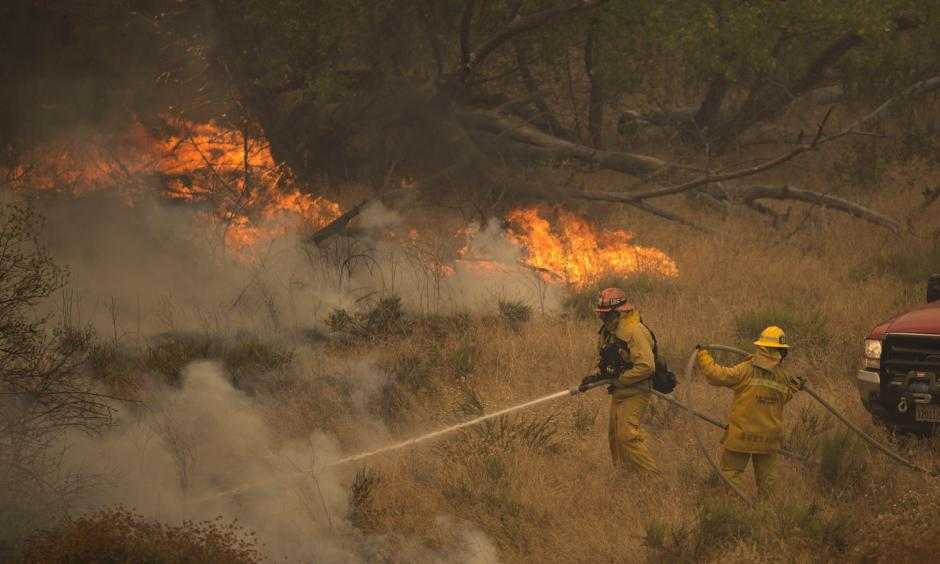 Firefighters retreat ahead of flames in Placerita Canyon north of Los Angeles on Sunday. The Sand Fire there has burned an estimated 33,000 acres of dry vegetation, and thousands of people have been evacuated from their homes. Photo: David McNew/Getty Images
