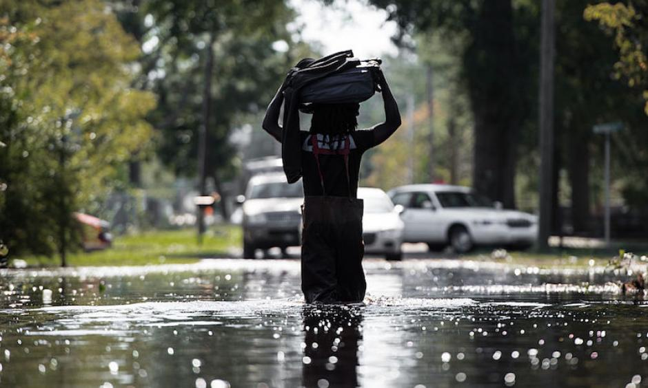 A man carries personal items through flooding associated with Hurricane Matthew on October 11, 2016, in Fair Bluff, North Carolina. Matthew, the Atlantic's first Category 5 hurricane since 2007, left a trail of destruction from the Lesser Antilles to Virginia. Haiti was hardest hit, with more than 500 deaths and nearly $2 billion in damage. Photo: Sean Rayford, Getty Images