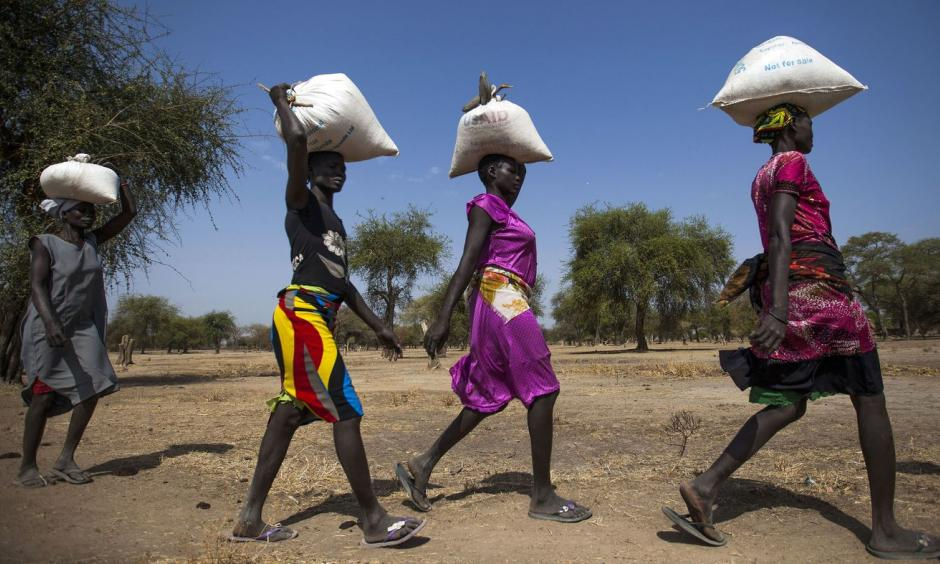 Women carry food in gunny bags after visiting an aid distribution center in South Sudan on March 10. Photo: Albert Gonzalez Farran, AFP, Getty Images
