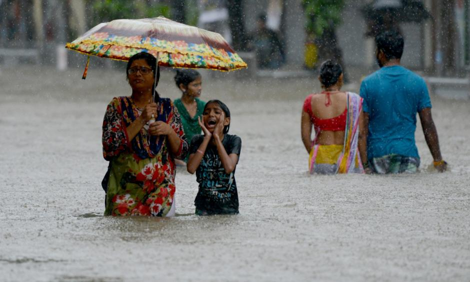 People wade through a flooded street in Mumbai, India, on August 29th, 2017. Photo: Punit Paranjpe, AFP/Getty Images