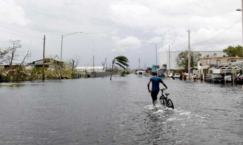 A man pushes his bicycle through a flooded street in Cataño, Puerto Rico, on Friday. Hurricane Maria drenched many spots on the island with about 20 inches of rain. Photo: Ricardo Arduengo/AFP/Getty Images