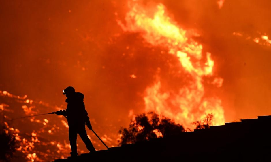 California resident waters a roof as the Thomas Fire approaches the town of La Conchita early Thursday morning. Photo: Wally Skalij, Los Angeles Times/Getty