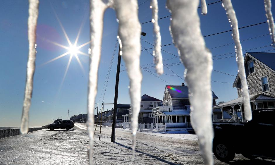 Icicles hang from a porch on Ocean Street as cleanup takes place in the Brant Rock section of Marshfield, MA, following a winter storm that flooded much of the area the previous day, on Jan. 5, 2018. Photo: John Tlumacki, The Boston Globe via Getty Images