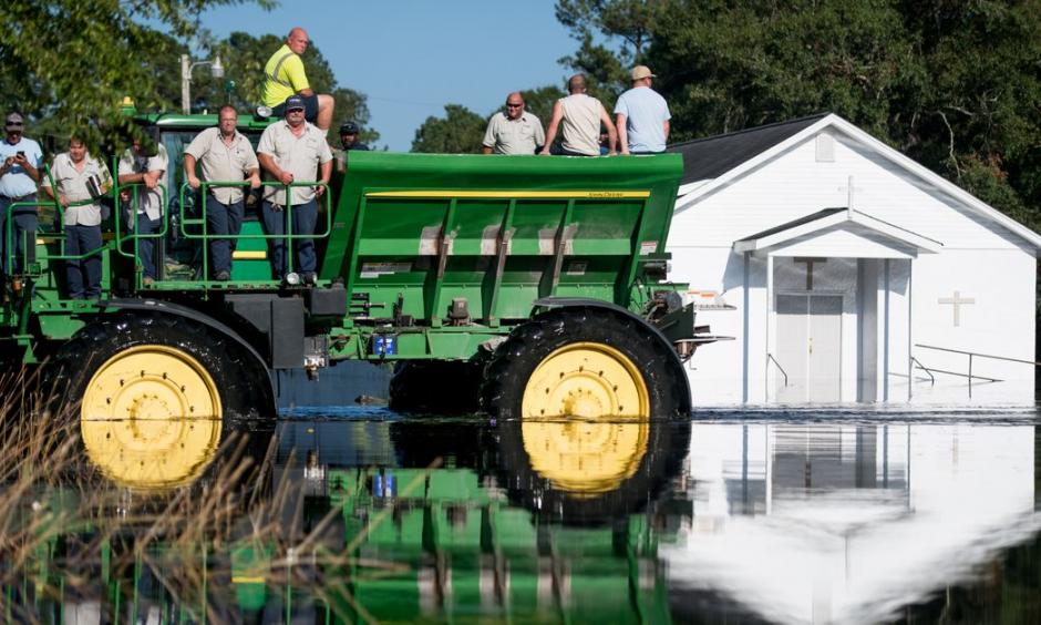 Workers use farm machinery to navigate floodwaters from the Waccamaw River caused by Hurricane Florence in Bucksport, South Carolina. Sea-level rise exacerbated flooding from the storm. Photo: Sean Rayford, Getty Images