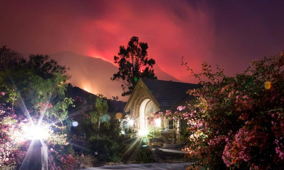 The Thomas Fire burns behind houses in Ojai, California, December 7, 2017. Photo: Kyle Grillot, AFP/Getty Images