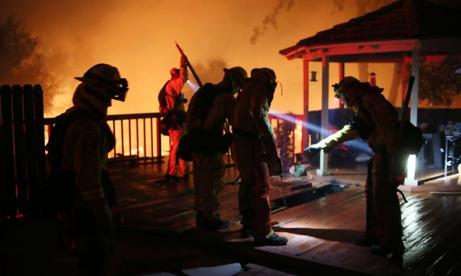 Firefighters work to save a home from an encroaching fire during the Lilac fire in Bonsall, California on Thursday, December 7, 2017. Credit: Sandy Huffaker, AFP, Getty Images