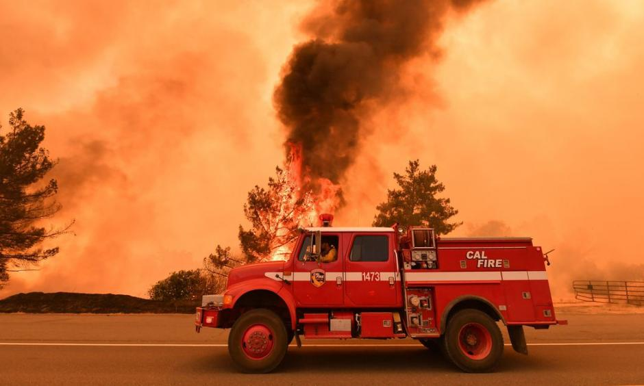 Firefighters work to control a fire as flames from the County Fire jump across Highway 20 near Clearlake Oaks, California, on July 1, 2018. Photo: Josh Edelson, AFP/Getty Images