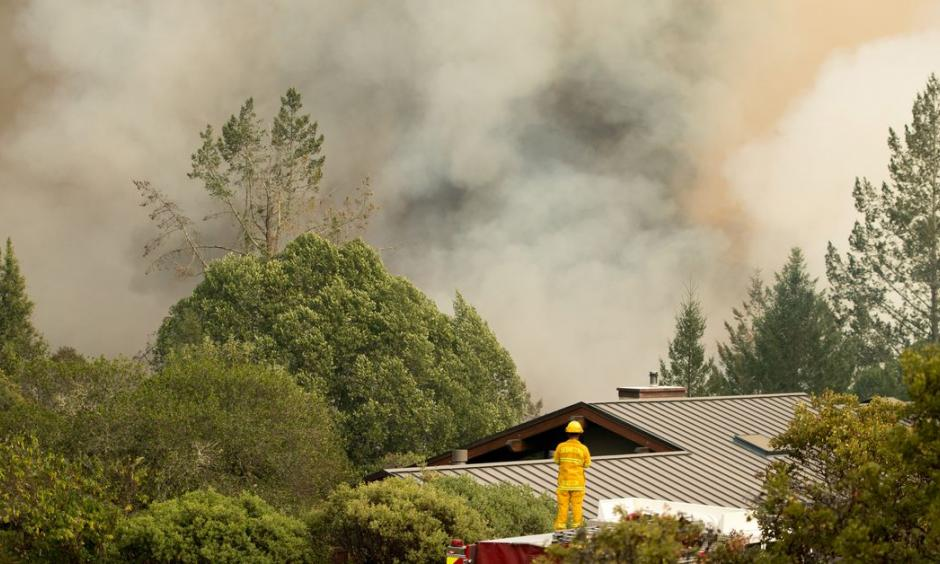 A firefighter watches smoke billow as flames approach a residential area in Sonoma in California in October. Photo: Josh Edelson, AFP/Getty Images