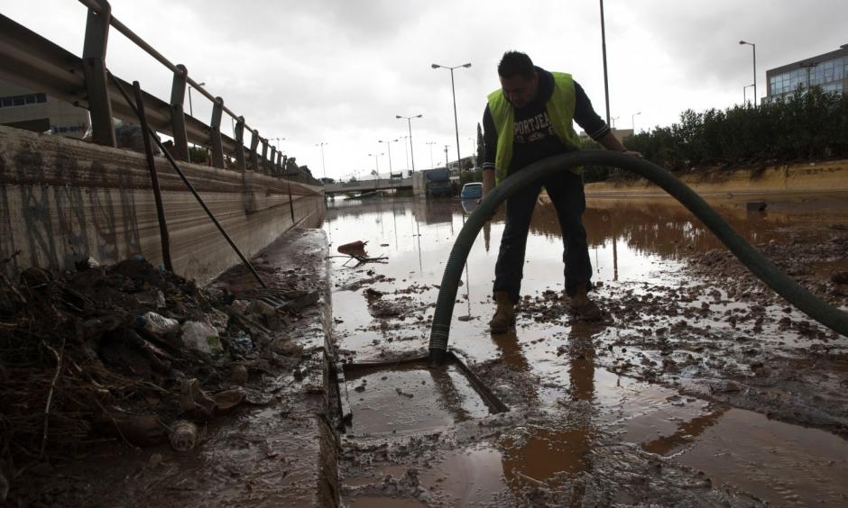 A worker tries to clean a sewer as water covers an interchange of a highway in Elefsina, western Athens, on Wednesday, Nov. 15, 2017. Flash floods in the Greek capital's western outskirts Wednesday converted roads into raging torrents of mud and debris, killing at least five people and inundating homes and businesses. Photo: Petros Giannakouris/Associated Press