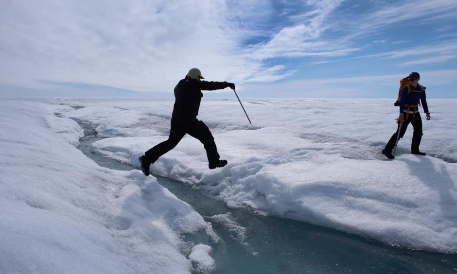 A scientist leaps over water during a trip to the Greenland ice sheet, which saw melting over more than 50% of its surface last year. Photo: Joe Raedle/Getty Images