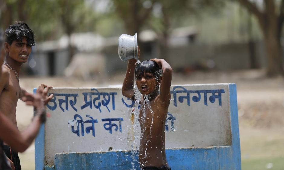 Indian boys bath at a drinking water tap on a hot day in Prayagraj, India. Photo: Rajesh Kumar Singh, AP