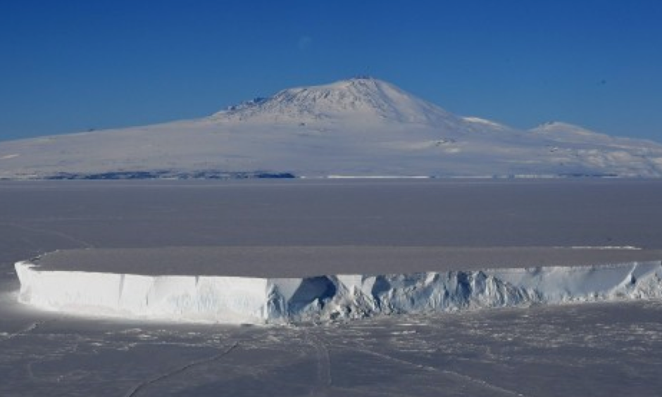 An iceberg lies in the Ross Sea with Mount Erebus in the background near McMurdo Station in Antarctica, November 11, 2016. A sheet of meltwater lasted for as long as 15 days in some places on the surface of the Ross Ice Shelf, the largest floating ice platform on Earth, during the Antarctic summer of 2016. Photo: Agence France-Presse via Getty Images