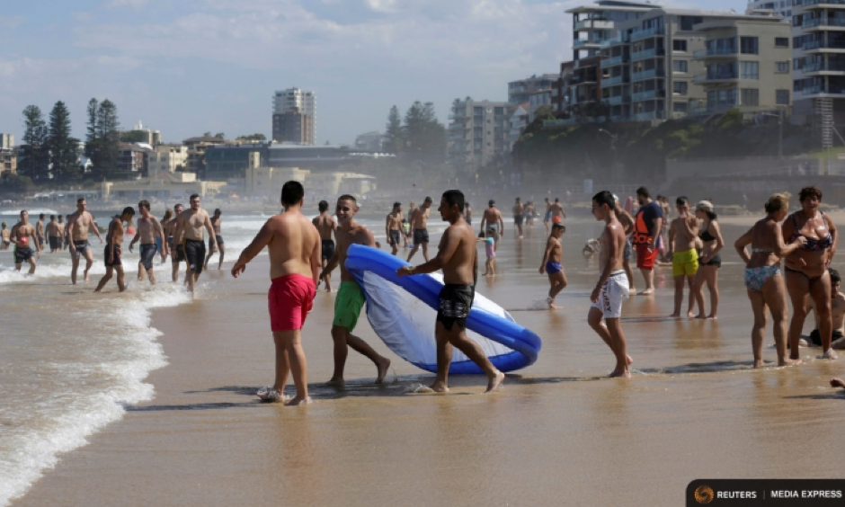 Sydneysiders take refuge from sweltering conditions alongside apartments at Sydney's North Cronulla Beach during a heatwave along Australia's east coast on Feb. 11, 2017. Photo: Jason Reed, Reuters