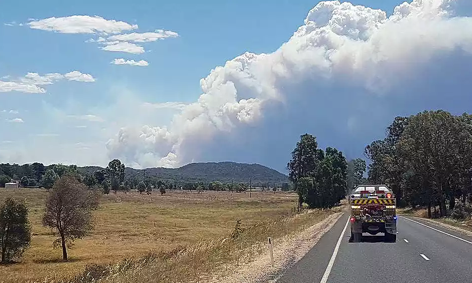 Smoke rises from the Sir Ivan fire near Coonabarabran on Sunday. Fire crews were waiting to assess damage on Monday as cooler weather brought some relief from the fire threat. Photo: Associated Press