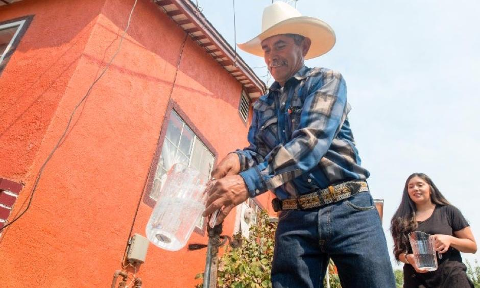 Homeowner Leonicio Ramirez and daughter Tania Ramirez are the first residents to receive water through a water distribution system in East Porterville, California, on Aug. 19, 2016. Engineers at the California Department of Water Resources designed a system to deliver water from the city of Porterville to 1,800 homes in its neighboring community to the east. Photo: Florence Low, California Department of Water Resources