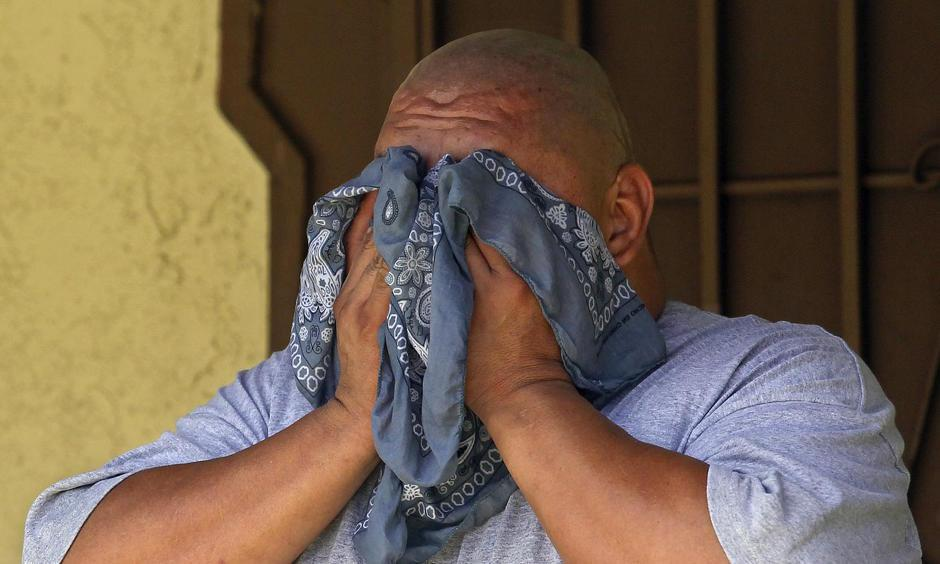 A man wipes his face in front of his home on Logan Street in Los Angeles. Mel Melcon, Los Angeles Times