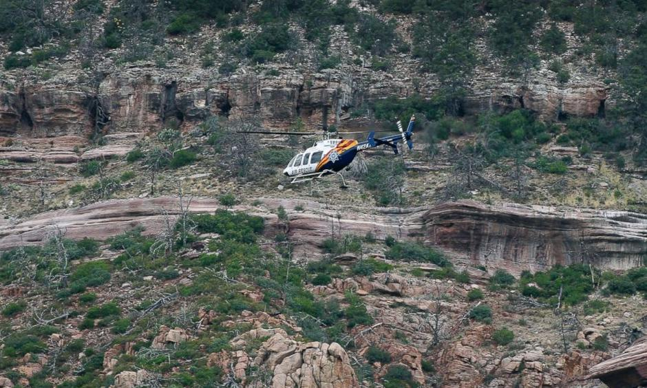 A helicopter flies above the rugged terrain along the banks of the East Verde River during a search and rescue operation for victims of a flash flood, July 16, 2017, in Payson, Ariz. Photo: ABC News