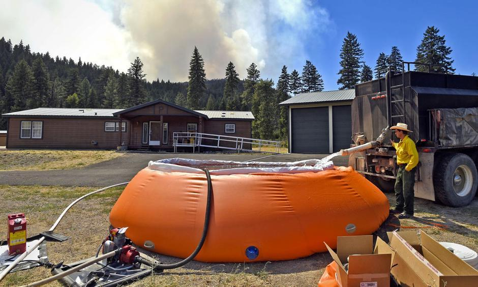 Nathan Smith of Arlee fills a 6,000 gallon portable tank with water at a residence off Quartz Road near Lozeau as smoke from the Sunrise fire rises in the background on Monday. On Wednesday, evacuations were ordered and the fire became the highest priority in the nation. Photo: Tom Bauer, Missoulian