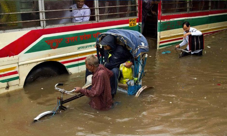 A man from a stranded passenger bus watches an Indian rickshaw puller negotiating through a waterlogged street following heavy rains in Allahabad, India, Tuesday, July 25, 2017. The monsoon season in India runs from June to September. Photo: Rajesh Kumar Singh, AP