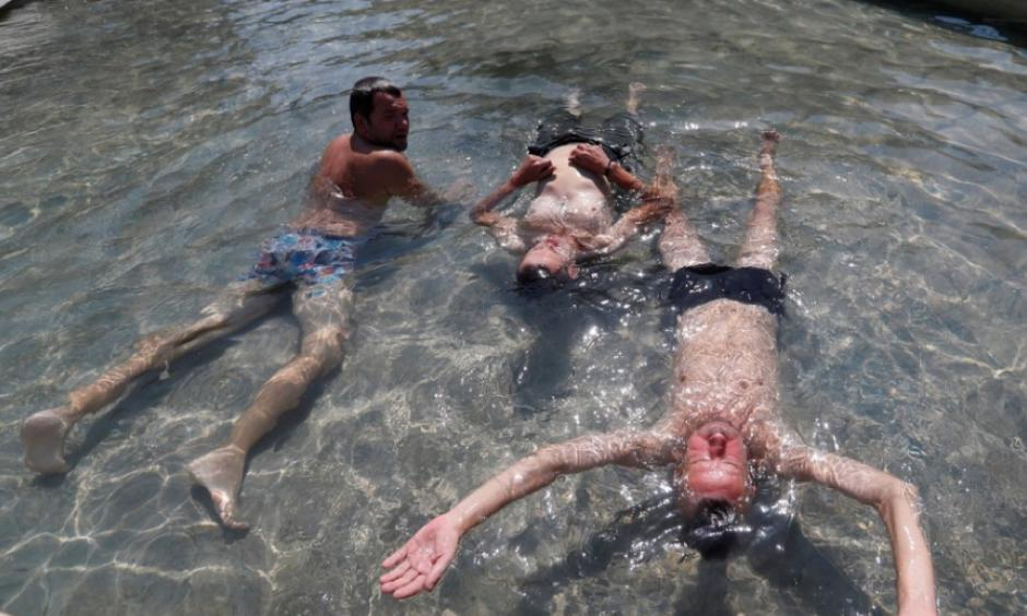 Men cool off in a fountain in Budapest, Hungary. Photo: Reuters