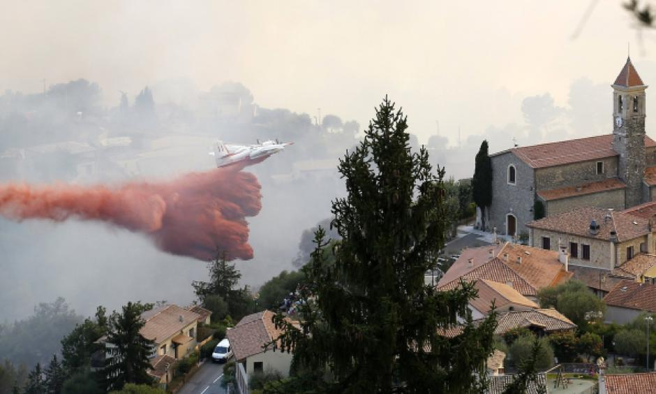A firefighting aircraft dumps its load on a forest fire in the town of Castagniers near Nice, southern France. Photo: EPA