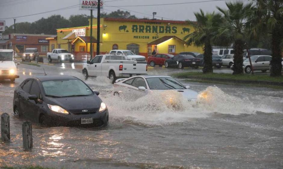 Traffic moves around a vehicle stalled in high water at the intersection of West Military Drive and Westbriar, Monday, August 7, 2017. Photo: Jerry Lara, San Antonio Express-News
