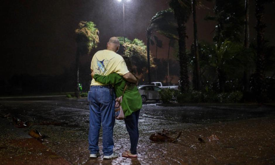 Tony Buchanan and Myava Buchanan watching heavy rain and winds from Hurricane Harvey on Friday night from a hotel in Corpus Christi, Tex. They had been evacuated from Aransas Pass, Tex. Photo: Tamir Kalifa, The New York Times