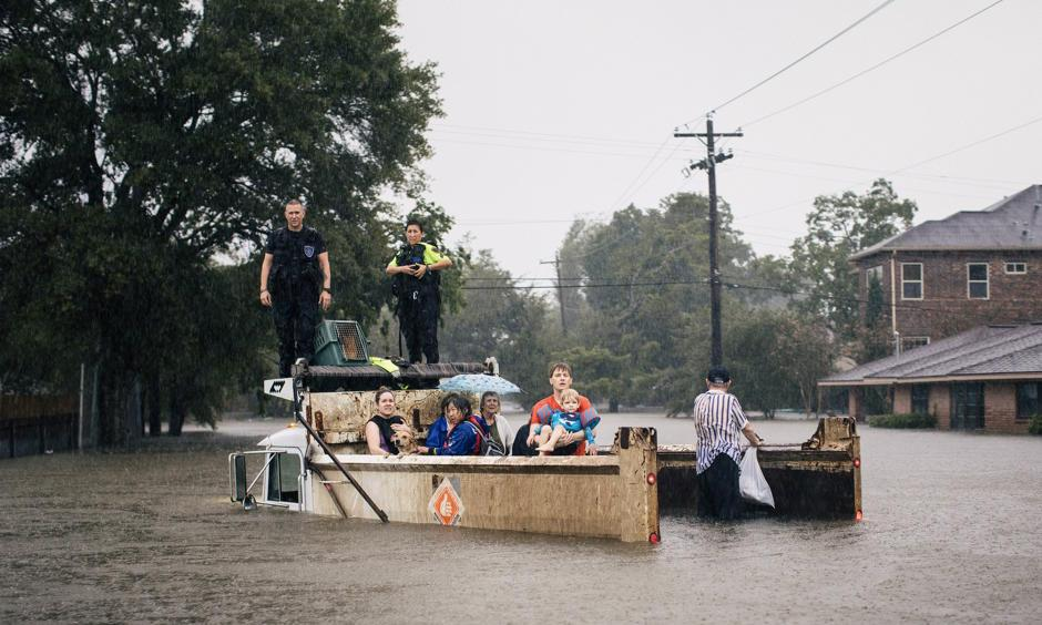 Rescue workers and civilians waited for emergency crews on Sunday in the Meyerland area of Houston. Photo: Alyssa Schukar, The New York Times