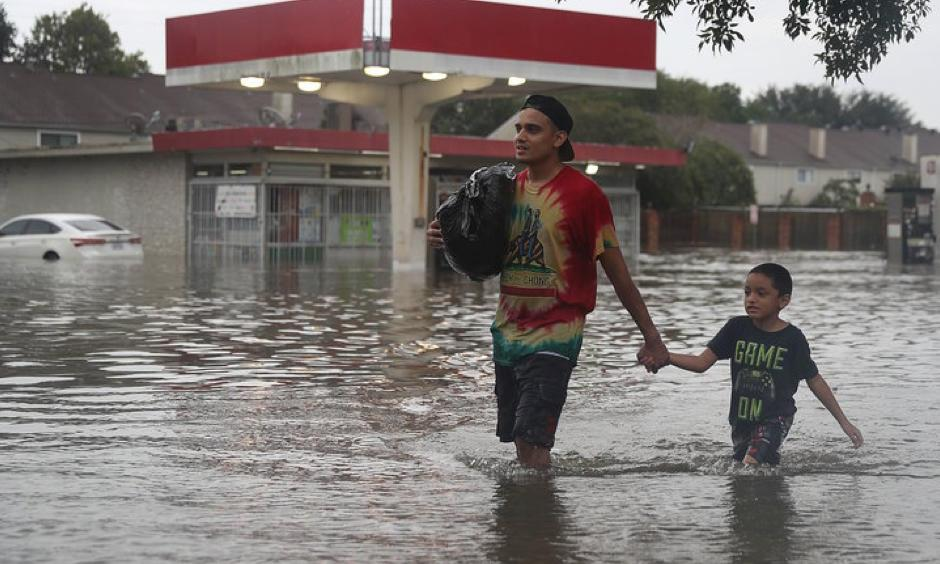 People walk down a flooded Houston street as they evacuate their homes Sunday after Hurricane Harvey hit. Joe Raedle, Getty Images