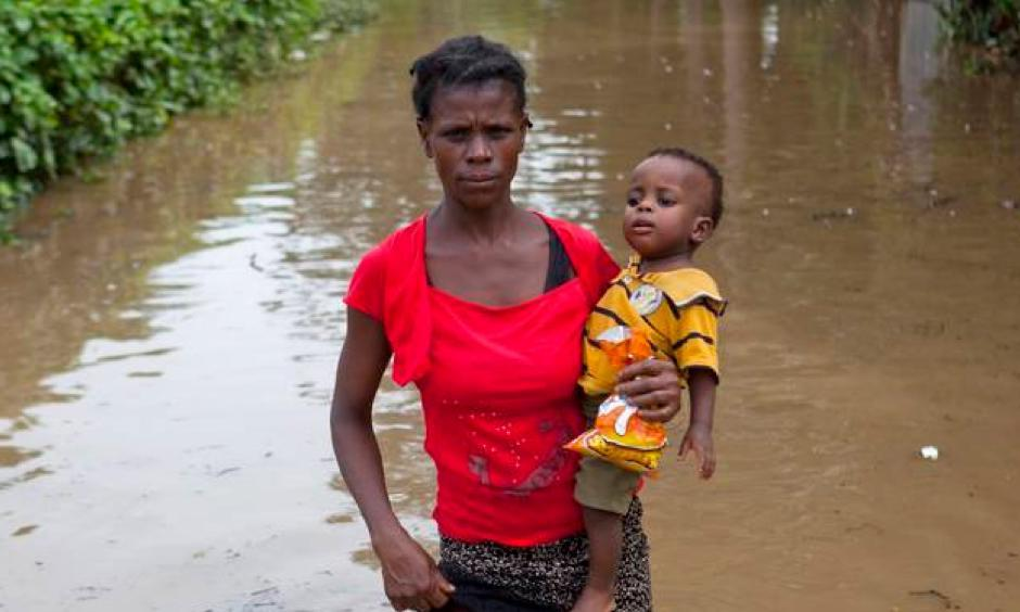 A woman carries her infant son across the flood waters of Hurricane Irma, in Fort-Liberte, Haiti, Friday Sept. 8, 2017. Irma rolled past the Dominican Republic and Haiti and battered the Turks and Caicos Islands with waves as high as 20 feet (6 meters). Photo: Dieu Nalio Chery, AP
