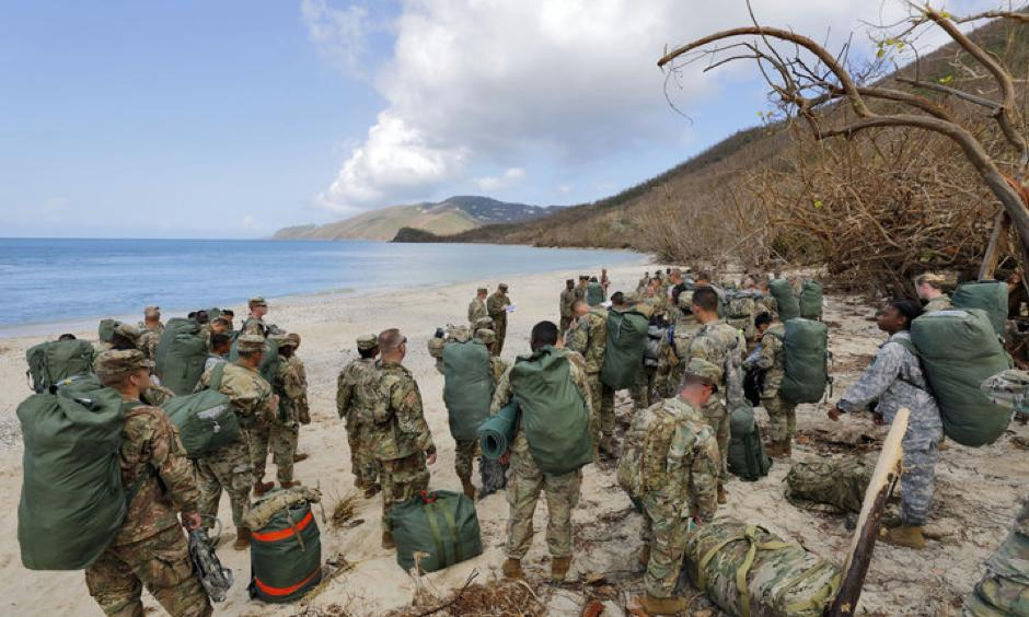 Army soldiers from the 602nd Area Support Medical Company gather on a beach as they await transport on a Navy landing craft while evacuating in advance of Hurricane Maria, in Charlotte Amalie, St. Thomas, U.S. Virgin Islands, Sept.17, 2017. Photo: Jonathan Drake, Reuters