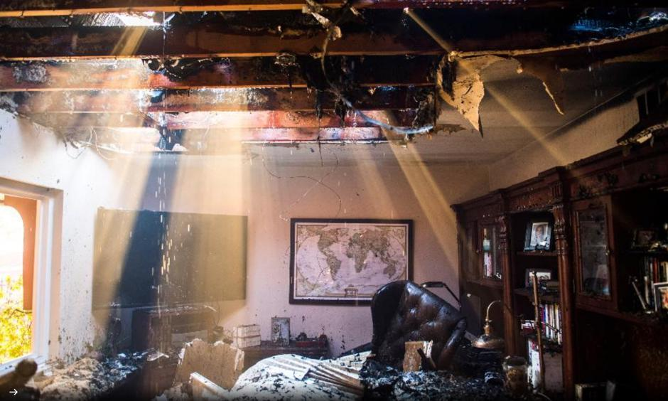 Smoke and water stream through the roof of a home destroyed by the Canyon Fire 2 on October 9th, 2017 in Anaheim Hills, California. At least six homes were burning by strong Santa Ana Winds forcing evacuations. The fire was estimated at over 2,00 acres. Stuart Palley, Los Angeles Times via Getty Images