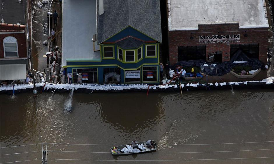 A boat carrying sandbags moves down South Central Avenue on Tuesday, May 2, 2017. As the floodwater from the Meramec River approached a record crest, the sandbags appeared to be holding back the water. Photo: David Carson, St. Louis Post-Dispatch