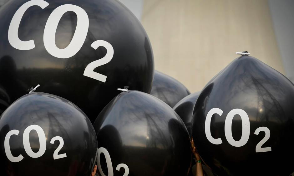 Activists hold giant balloons labeled 'CO2' in front of the Neurath coal power plant ahead of the Bonn climate summit. Photo: Philipp Guelland, EPA