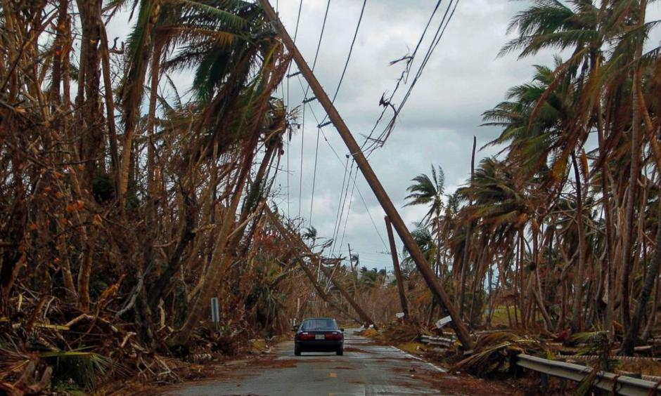 A car drives under tilted power line poles in the aftermath of Hurricane Maria in Humacao, Puerto Rico, Oct. 2, 2017. Photo: Ricardo Arduengo, AFP/Getty Images