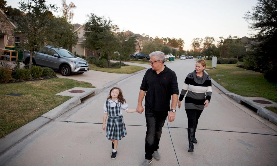 Leslie Martinez, right; her husband, John Ahearn; and their daughter, Alex Ahearn, outside their home, which flooded after Hurricane Harvey despite being outside the official flood plain in The Woodlands, Tex. Photo: Ilana Panich-Linsman for The New York Times