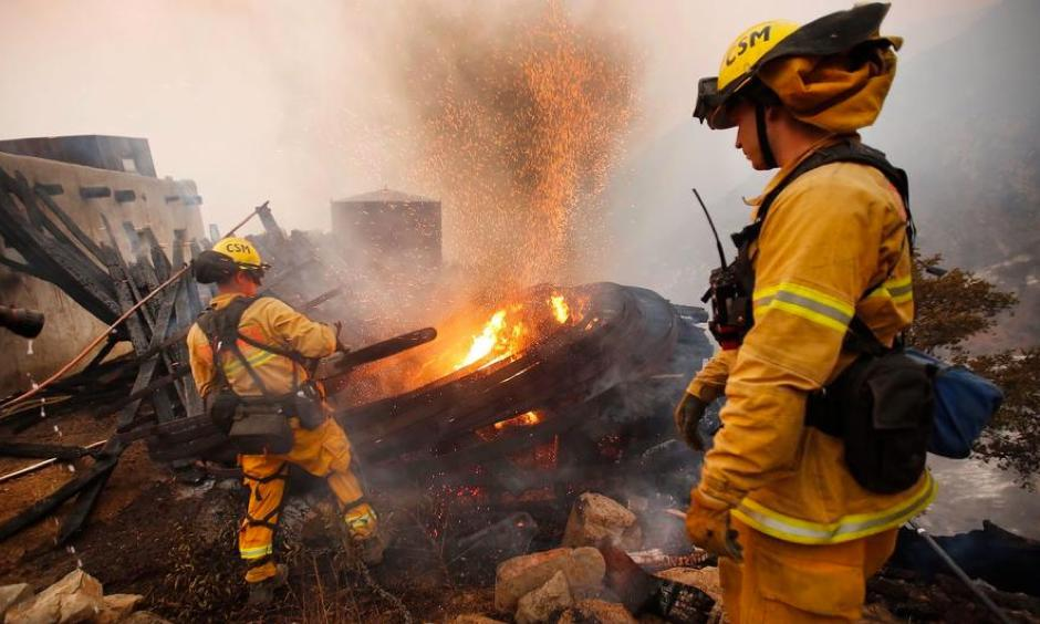 Firefighters work Dec. 12 to extinguish a burning structure that is threatening other buildings and homes high above Toro Canyon in Carpinteria. Photo: Al Seib, Los Angeles Times