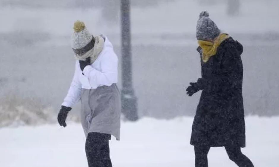 Pedestrians struggle to move amid gusty winds and snow in Denver as a winter storm swept over Colorado's eastern plains on Jan. 21, 2018. Photo: David Zalubowski, AP