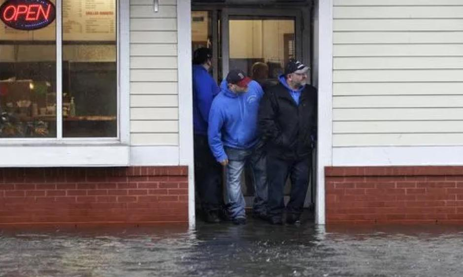 People stand at the entrance to a pizza shop as water floods a street, in Scituate, Mass., March 2, 2018. Photo: Steven Senne, AP