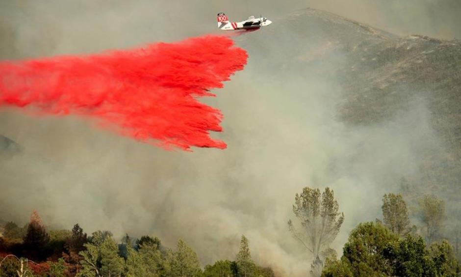 An air tanker drops retardant on a wildfire burning above the Spring Lakes community on Sunday, June 24, 2018, near Clearlake Oaks, Calif. Wind-driven wildfires destroyed buildings and threatened hundreds of others Sunday as they raced across dry brush in rural Northern California. Photo: Noah Berger, AP