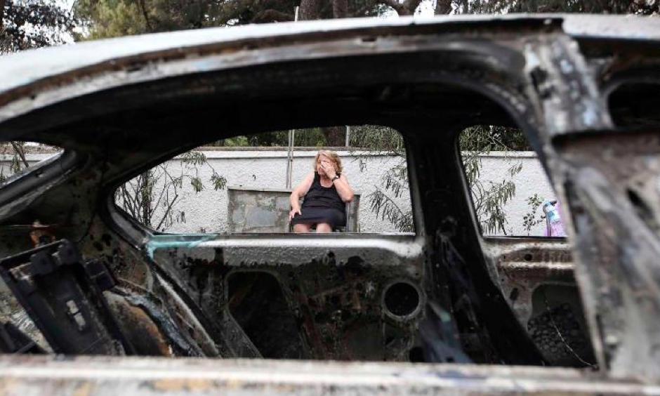 Asimina Psalti, 87, sits outside the remains of her burned house in Mati, Greece, on Tuesday, July 24. Photo: Thanassis Stavrakis, AP